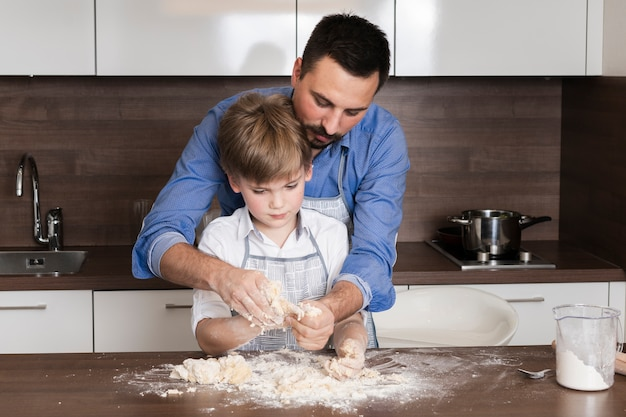 Low angle son and dad rolling dough