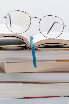 Low angle stack of books with glasses on top