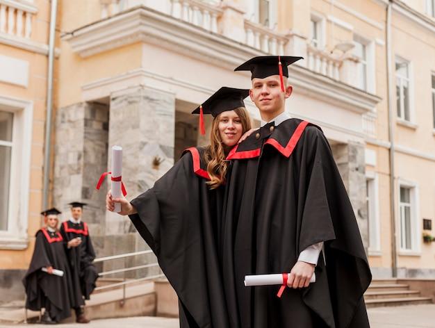 Низкий угол студентов с дипломом
