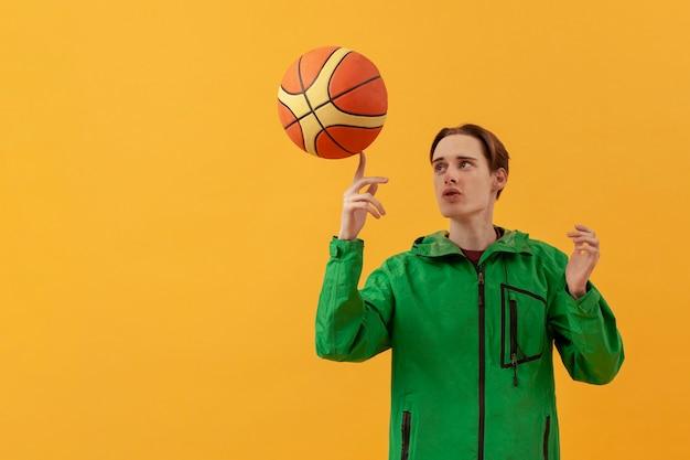 Низкий угол подросток играет с баскетбольным мячом