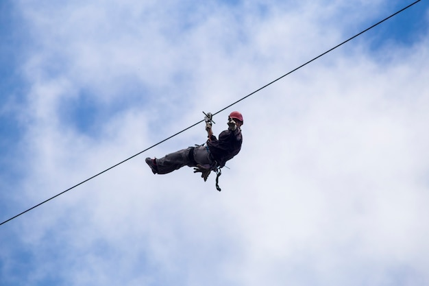 Low angle of tourist on zip line and gesturing against sky at costa rica