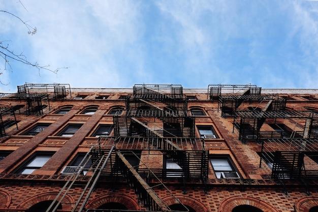 측면에 비상 금속 계단이있는 아파트 건물의 낮은 각도 업
