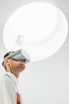 A low angle vertical photo of a futuristic cool male doctor wearing vr goggles in a hospital