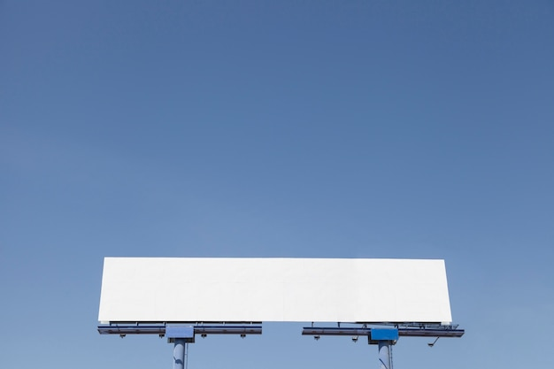 Low angle view of advertising billboard against blue clear sky