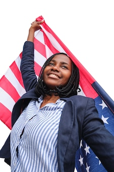 Low angle view of an african american woman smiling wrapped and holding with outstretched arms the u.s. flag on a white background.