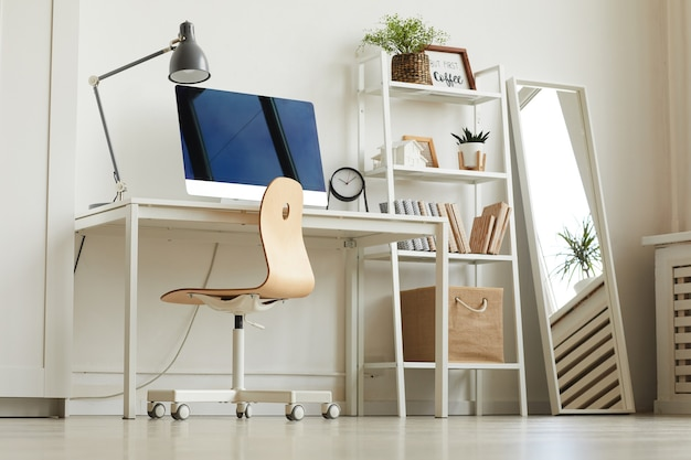 Low angle view at all-white home office workplace with wooden chair and modern computer on desk