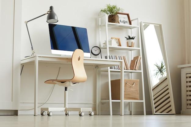 木製の椅子と机の上にモダンなコンピューターを備えた真っ白なホームオフィスの職場でのローアングルビュー