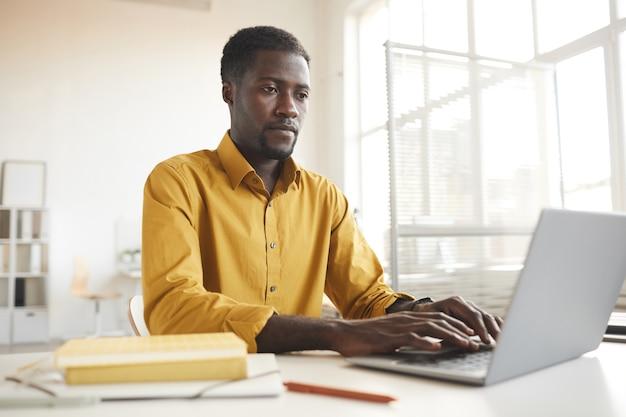 최소한의 사무실 인테리어, 복사 공간에 책상에서 작업하는 동안 노트북을 사용하는 현대 아프리카 계 미국인 남자에서 낮은 각도보기