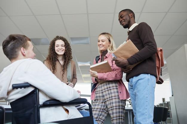 대학 도서관에서 함께 공부하는 동안 휠체어에서 젊은 남자와 이야기하는 학생들의 다민족 그룹에서 낮은 각도보기