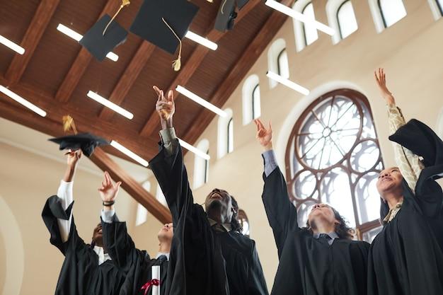 클래식 학교 강당에서 실내 졸업식 동안 모자를 던지는 다민족 젊은이들의 낮은 각도 보기, 복사 공간