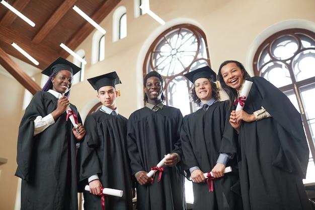 졸업 가운을 입고 학교 강당에 서서 행복하게 웃고 있는 카메라를 바라보는 다민족 젊은이들의 낮은 각도