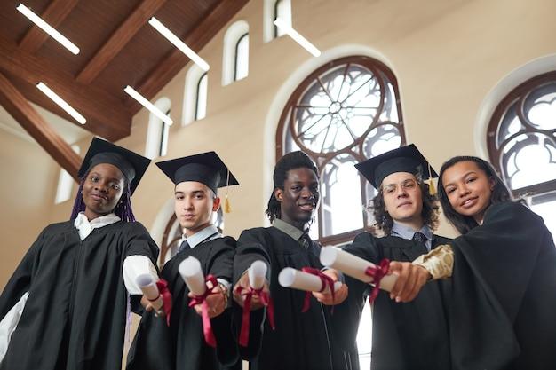 학교 강당에 서 있는 동안 졸업 가운을 입고 졸업장을 카메라에 가리키는 다민족 젊은이들의 낮은 각도 보기