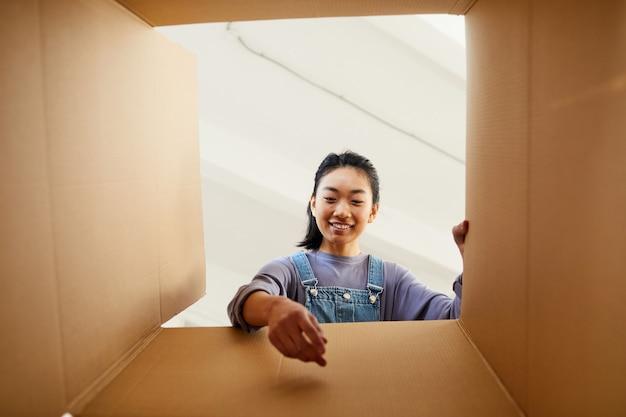 Низкий угол обзора улыбающейся азиатской женщины, которая тянется к картонной коробке при упаковке или распаковке для нового дома