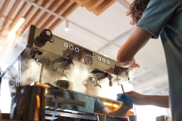 Низкоугольный вид на дымящуюся кофеварку в кафе или кофейне с неузнаваемым бариста, делающим свежий кофе, копией пространства