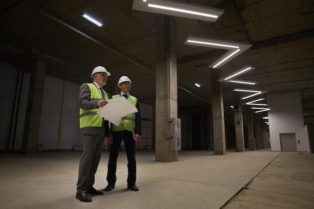 건설 현장에 서있는 동안 안전모를 착용하고 계획을 잡고있는 두 명의 비즈니스 사람들의 낮은 각도보기,