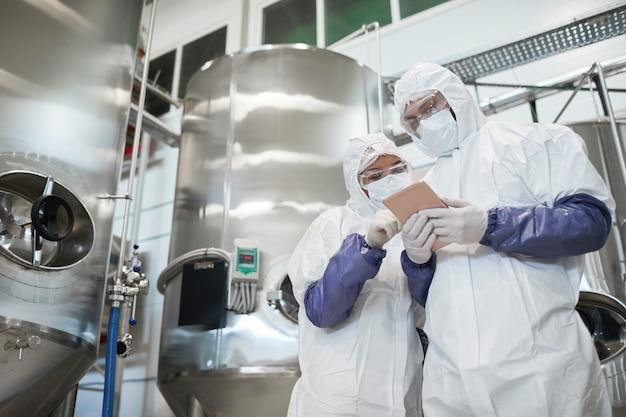 현대 화학 공장에서 디지털 태블릿을 사용하는 동안 보호복을 입은 두 작업자의 낮은 각도 보기, 복사 공간