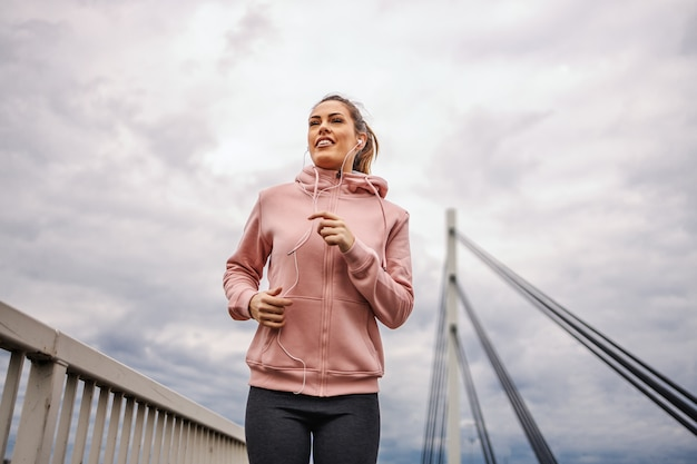 Low angle view of attractive highly motivated sportswoman with healthy habits listening music and running on the bridge on cloudy weather. fitness outdoors concept. urban life.
