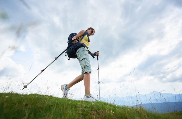 Low angle view of attractive woman tourist hiking in carpathian mountain trail, walking on grassy hill, using trekking sticks, enjoying summer day. lifestyle concept