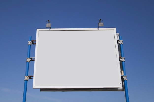 Low angle view of blank hoarding with lights against blue sky