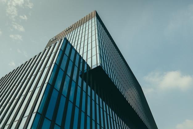 Vista di angolo basso di una costruzione in una facciata di vetro sotto il bello cielo nuvoloso