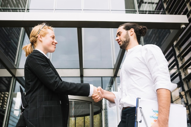Low angle view of businessman and businesswoman shaking each other hands