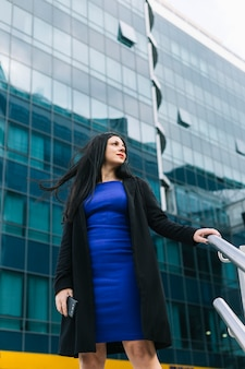 Low angle view of businesswoman standing in front of office building