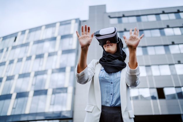 Low angle view of charming muslim businesswoman standing in front of her corporate firm and using vr goggles. millennial generation.
