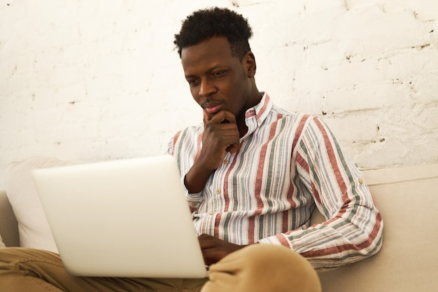 Low angle view of concentrated attractive young afro american student sitting on sofa with laptop