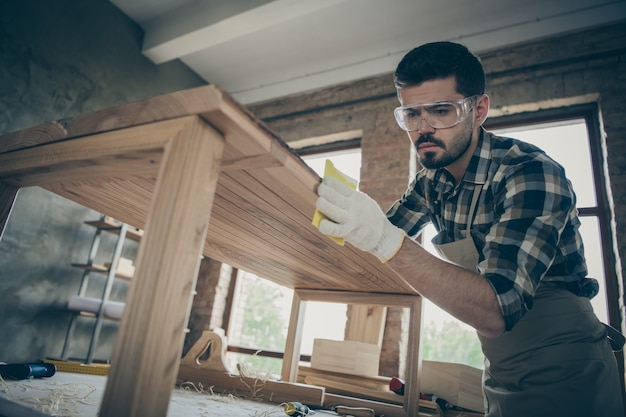 Низкий угол обзора концентрированный рабочий из твердых пород дерева обновляет деревянную мебель, стол, полирует гладкую поверхность в домашнем гараже