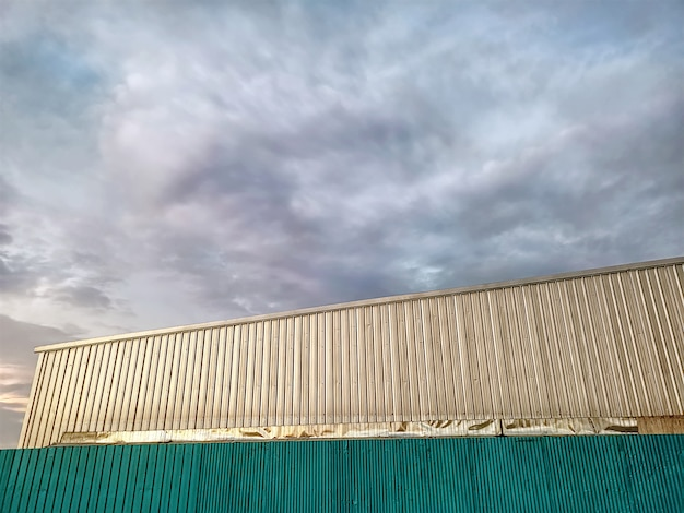 Low angle view of corrugated fence and wall outside warehouse against cloudy sky