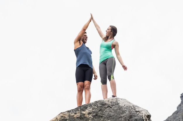 Low angle view of couple giving high five on rock