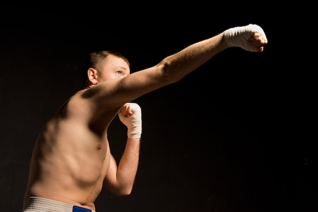 Low angle view in darkness of a fit young boxer