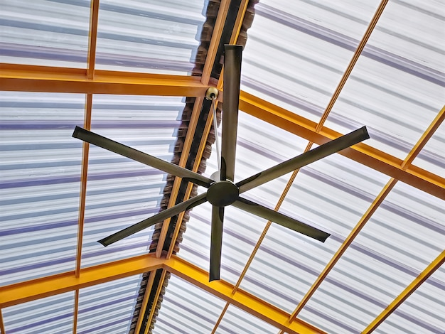 Low angle view of electric ceiling fan under yellow roof structure