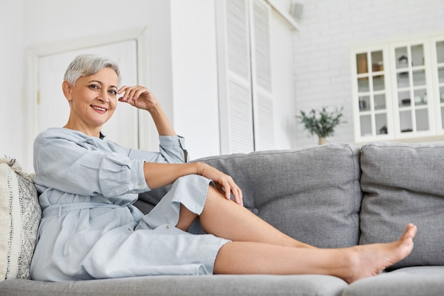 Low angle view of fashionable elegant mature sixty year old caucasian woman with short pixie hairstyle relaxing at home sitting on gray sofa in her spacious cozy clean living room, smiling
