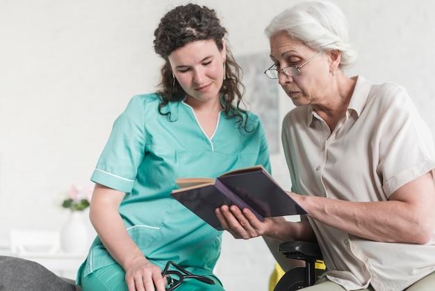Punto di vista di angolo basso dell'infermiere femminile che esamina il libro di lettura senior della donna