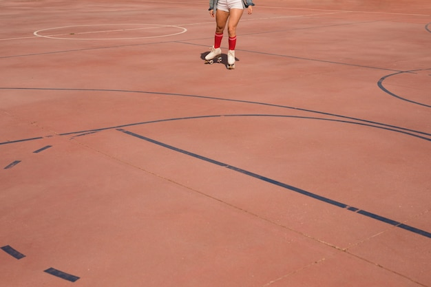 Low angle view of female skater skating on court