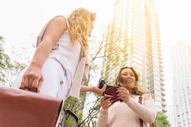 Punto di vista di angolo basso del turista femminile che dà passaporto al suo amico contro grattacielo