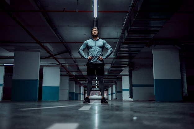 Low angle view of fit handsome caucasian sportsman in active wear standing in underground garage with hands on hips. urban life concept.