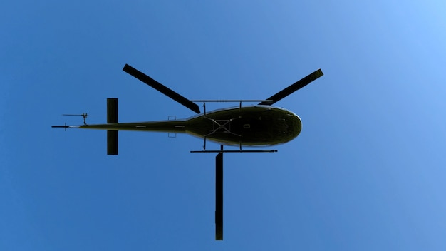 Low angle view of flying black metal helicopter on blue sky.