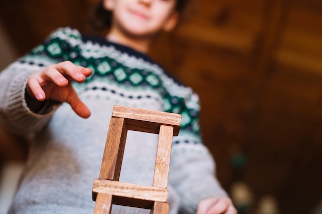 Low angle view of girl's hand playing with stacked wooden blocks