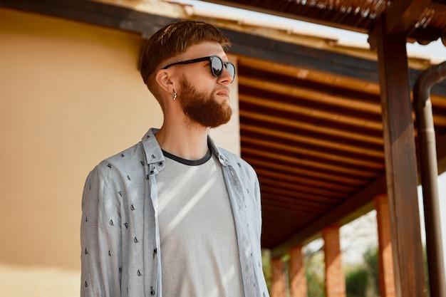 Inquadratura dal basso di bell'uomo giovane europeo bello in vestiti alla moda