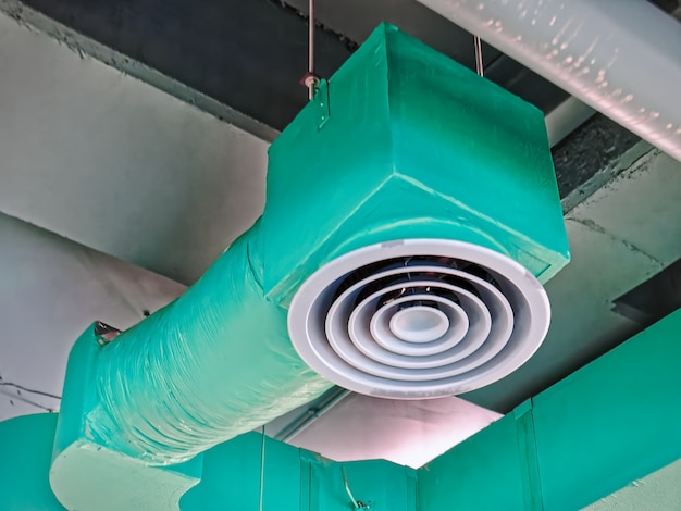 Low angle view of green insulated air conditioning duct with round grille diffuser