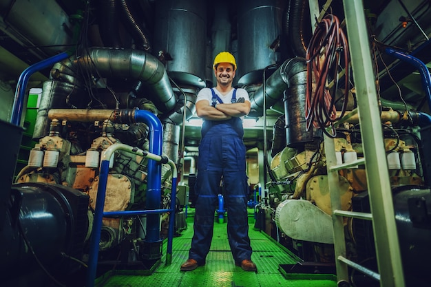 Low angle view of handsome caucasian worker in overall and helmet on head standing in ship next to engine with arms crossed.