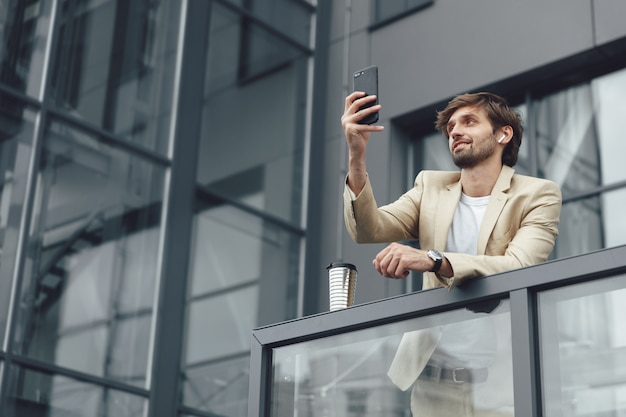 Low angle view of handsome man in formal wear having video chat on smartphone while standing on balcony of office center