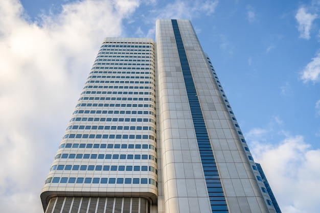 Inquadratura dal basso di un edificio alto con finestre blu sotto un cielo nuvoloso e luce solare