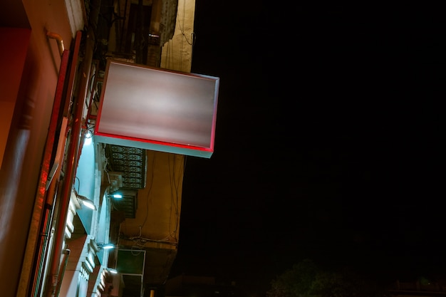 Low angle view of illuminated billboard on residential building against sky