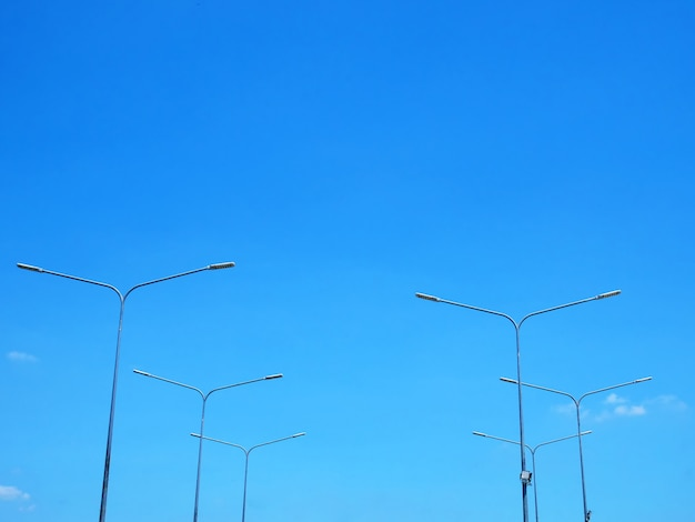 Low angle view of lamp posts against blue sky at day time