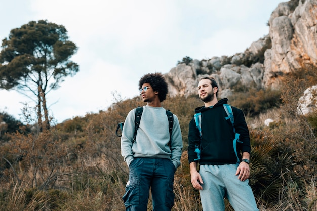 Low angle view of male multi ethnic hikers