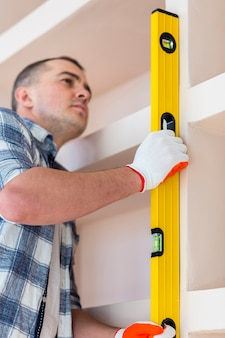 Low angle view of man holding spirit level