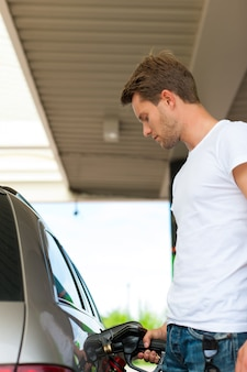Low-angle view of man refueling car at gas station